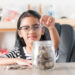 little girl in putting coin in to glass jar for saving money