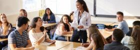 Une femme, debout dans une salle de classe, parle avec des étudiants.