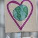 Une pancarte illustrant un cœur autour de la Terre est présentée pendant une manifestation.