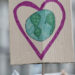 A protest sign with a drawing of a heart surrounding the Earth.