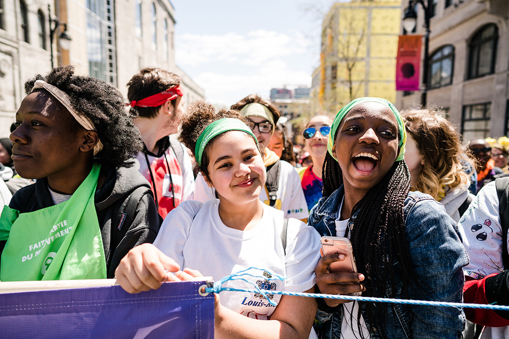 Smiling young people at the front of a group who is marching in the streets.
