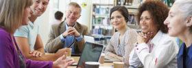 Des adultes discutent entre eux à une table dans une bibliothèque.
