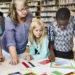 Un groupe d'élèves et une enseignante étudient une carte de la Terre et des drapeaux.
