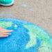 Un enfant dessine la planète Terre avec de la craie.