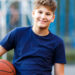 A boy holds a basketball under his arm in front of a playground.