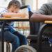 Des enfants assis à leurs bureaux, incluant un élève noir en fauteuil roulant, font leurs travaux.