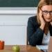 Une enseignante ressent des maux de tête en étant assise à son bureau, devant son ordinateur.