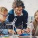 Autour d'une table où se trouvent des modèles d'éoliennes, des élèves et un enseignant travaillent avec leurs appareils électroniques et leurs notes.