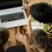 Un groupe d'élèves, vu du haut, discutant de leurs devoirs avec l'aide d'un ordinateur portable.