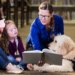 A teacher next to a therapy dog reads a book to a group of students.
