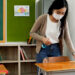 Young female teacher using an alcohol spray to disinfect student desks in classroom.