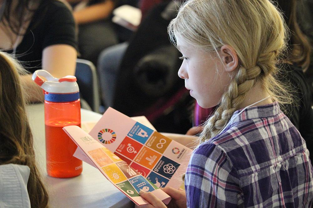 Une fille lit un livret qui contient une liste des objectifs de développement durable.