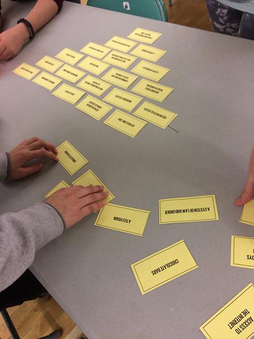 Des enfants organisent en forme de pyramide des cartes sur lesquelles on peut lire divers items.