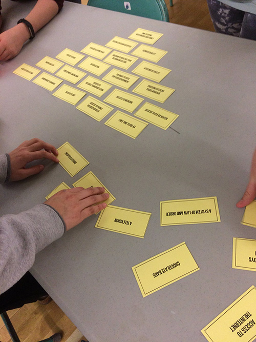 Children organize in a pyramid shape various cards, each with an item written on them.