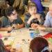 Un groupe d'enfants et un adulte jouent un jeu de société.