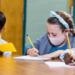Un groupe d'enfants portant des maques écrivent dans leurs cahiers.