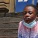 Une fille noire avec un masque autour du cou est assise sur les marches devant une école.