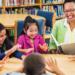 Une enseignante lit un livre à un groupe de jeunes enfants autour d'une table à la bibliothèque.
