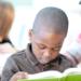 Teacher in classroom helping student read