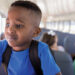 Standing on bus seat, elementary boy is unhappy about school