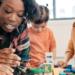 Teachers helping JK students with building block