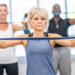 Mature women exercising with people in the background